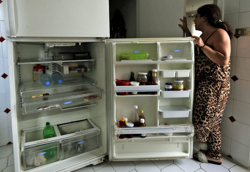 woman standing with her fridge open