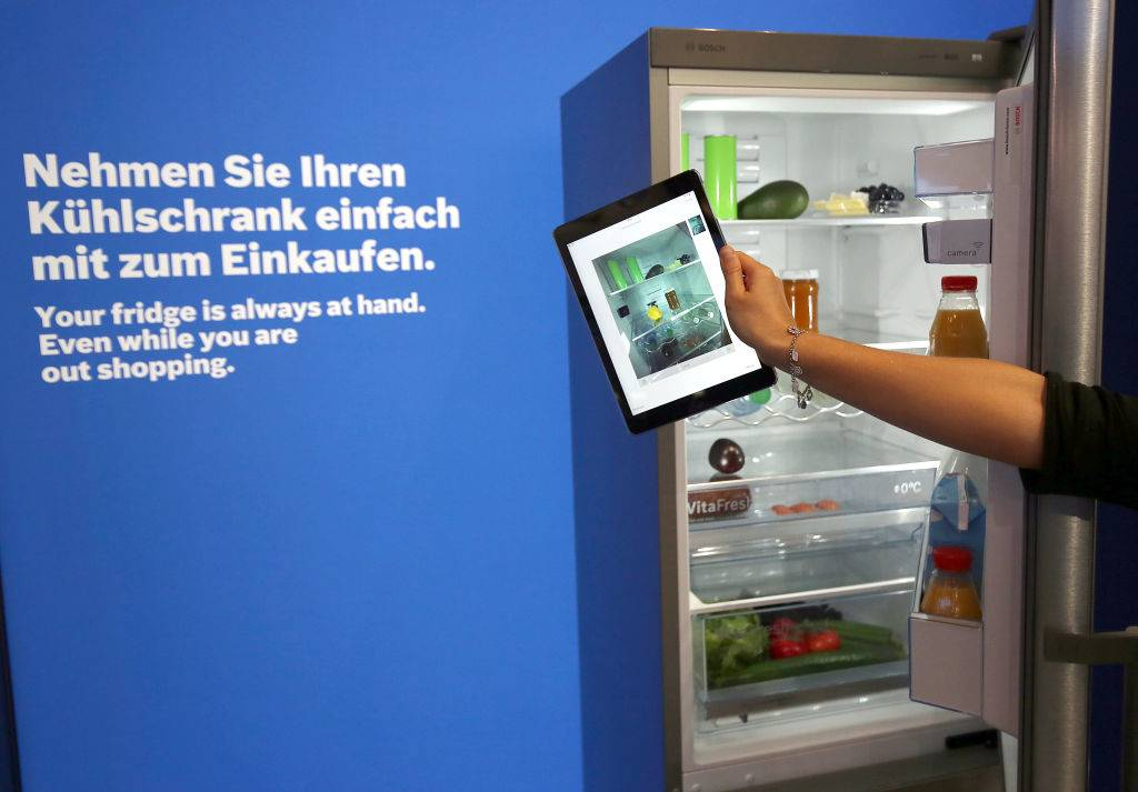 woman taking a photo of a fridge with an ipad