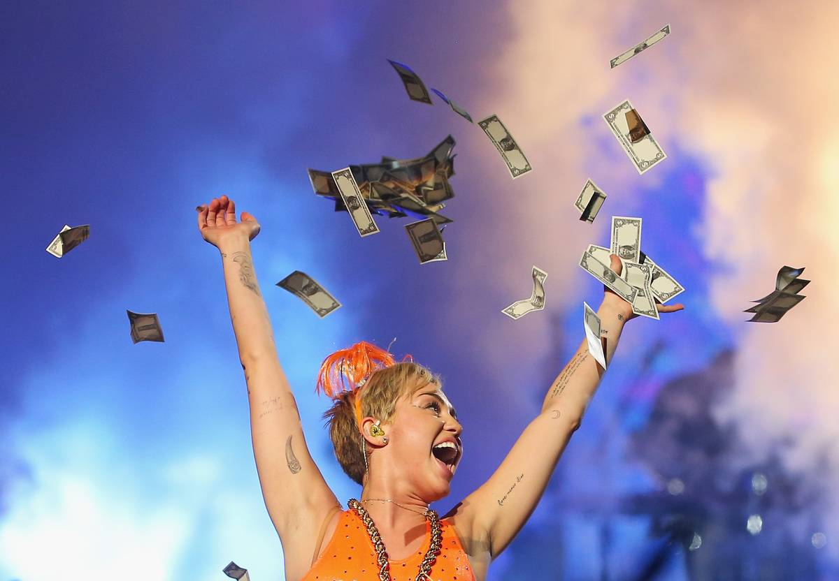 Dollar bills rain down on Miley Cyrus during a concert.