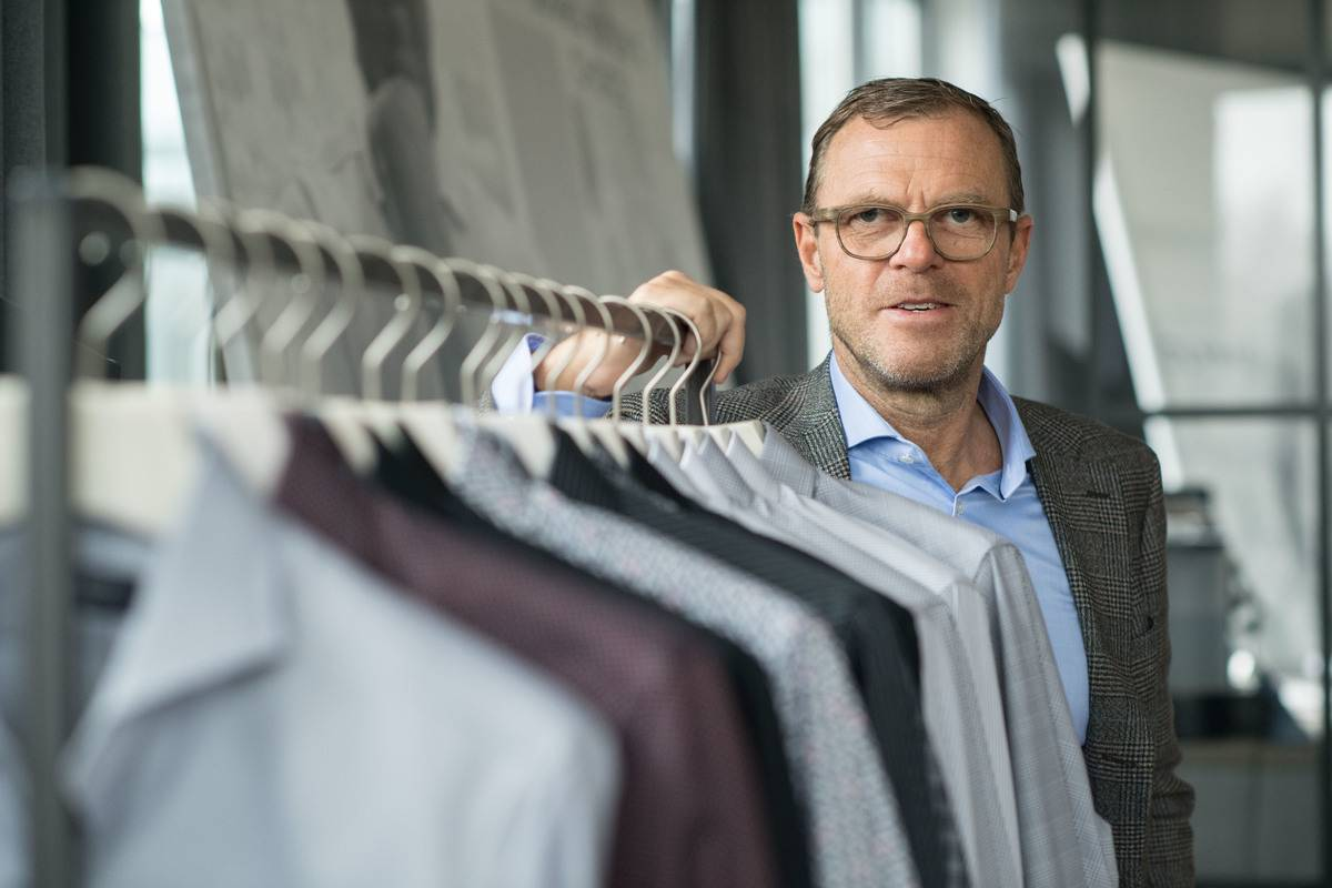 The CEO of the shirt company Olymp stands next to a rack full of shirts.