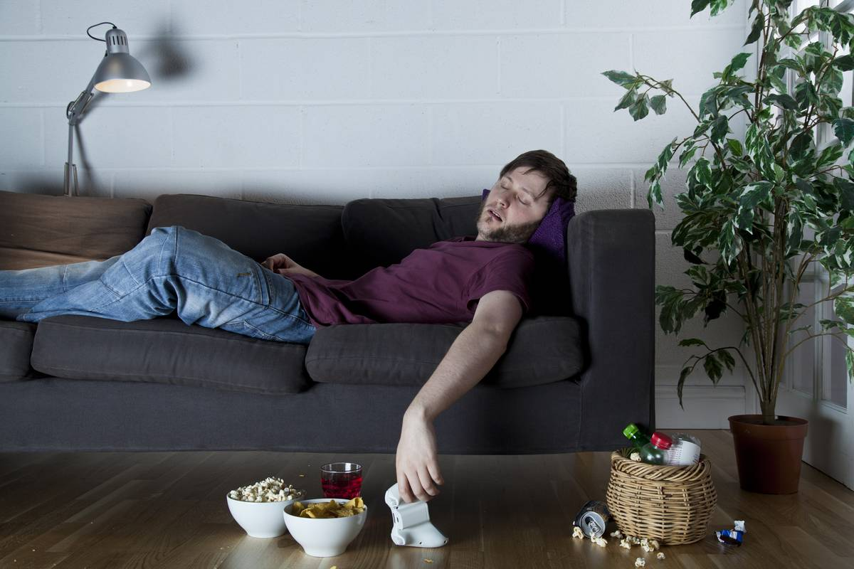 A man falls asleep while playing video games.