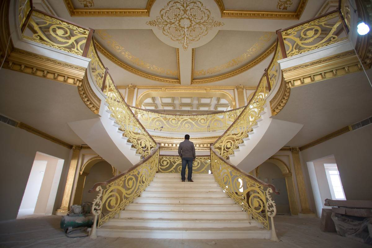 A man stands on a staircase in a $20 million house.