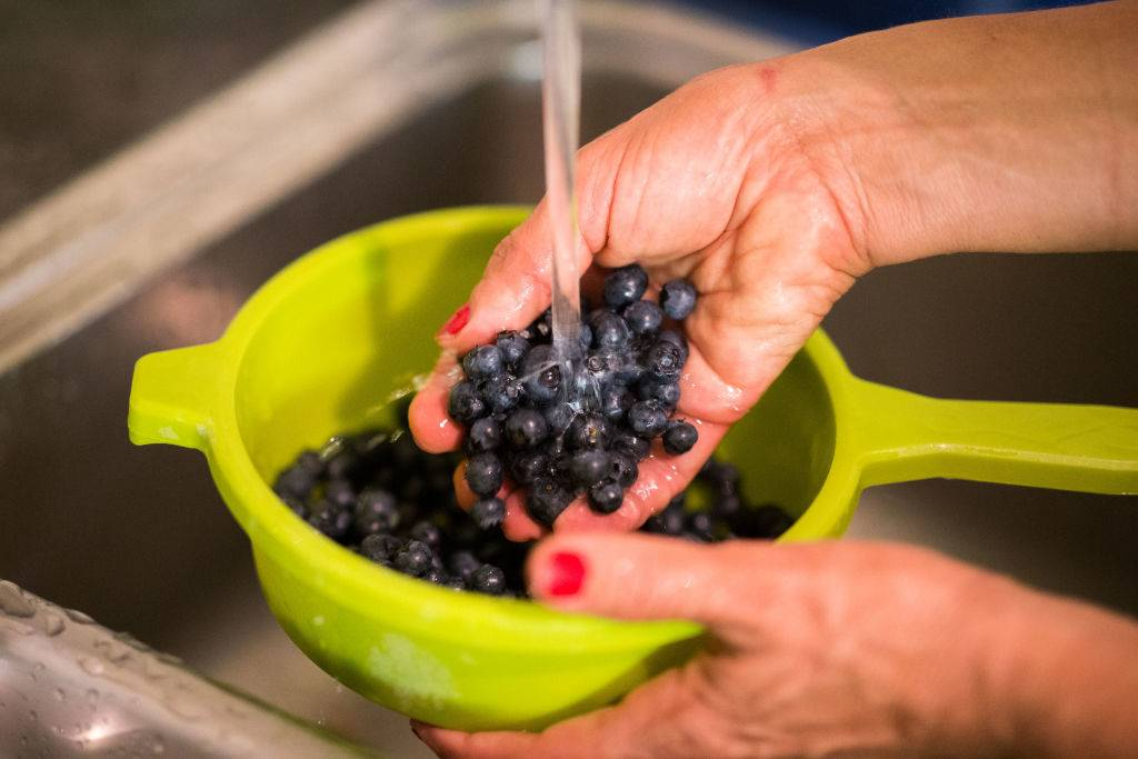 A woman washing blueberries