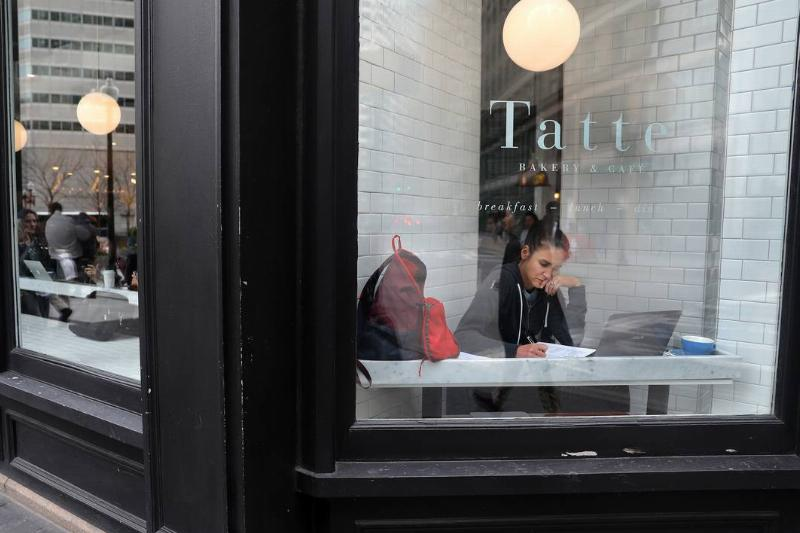 A woman works in front of a coffee shop window.