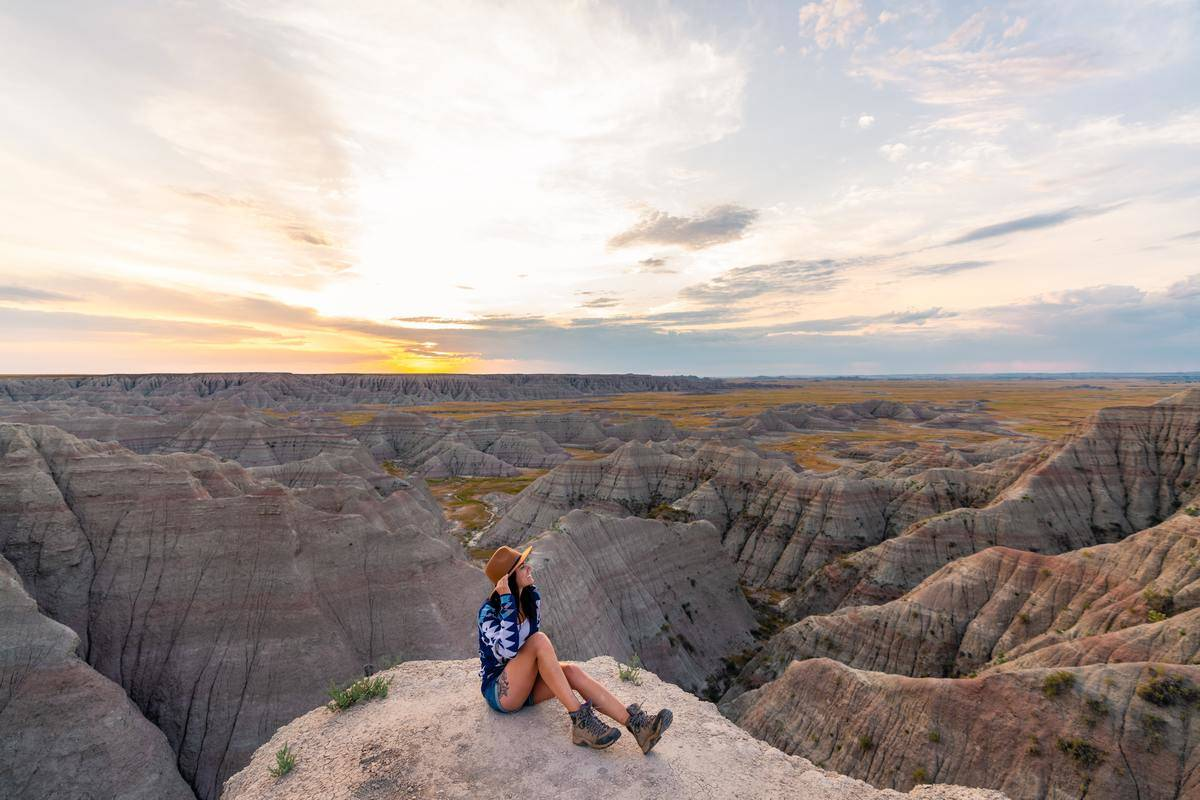 A woman sits on a rock in Badlands National Park.
