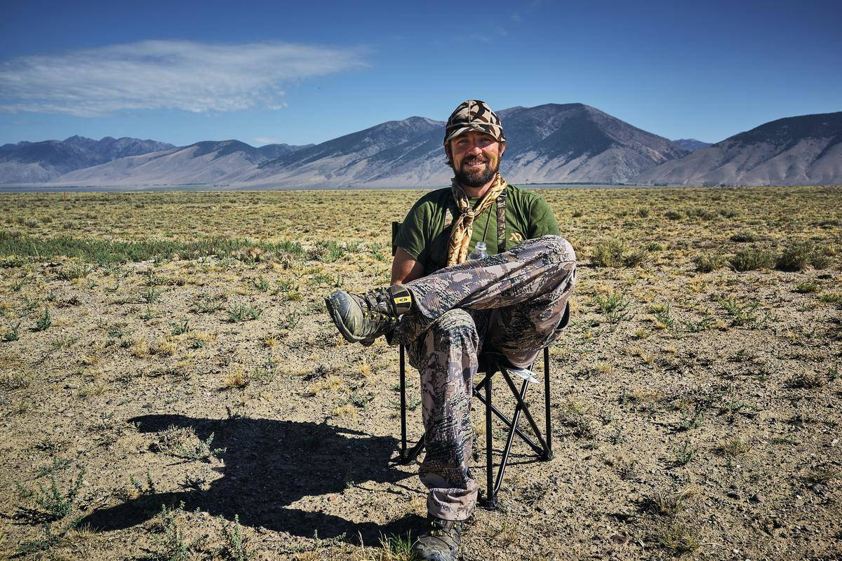 A man sit in a chair in the middle of an Idaho expanse.
