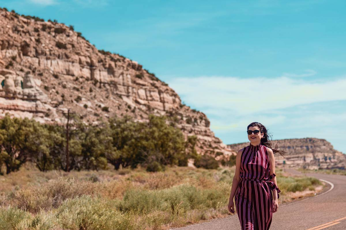 A woman stands on a windy road in New Mexico.