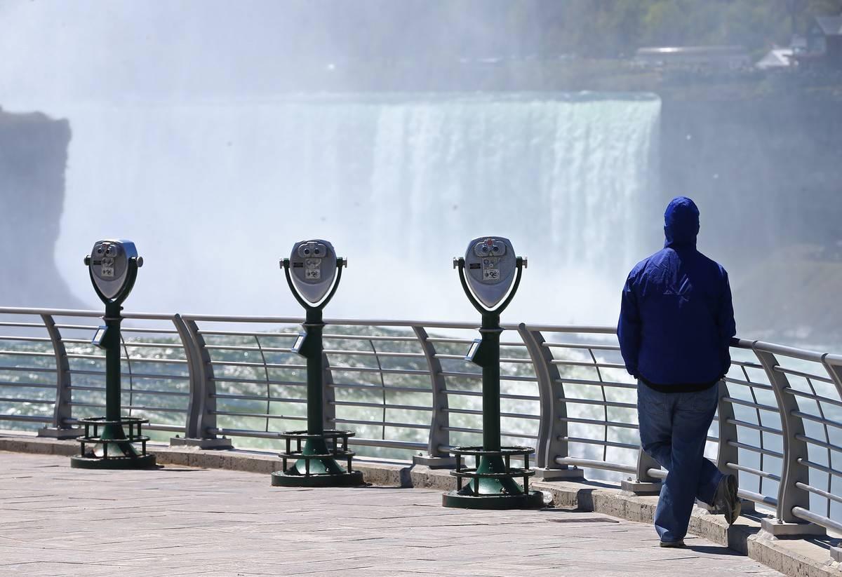 A man looks at Niagara Falls.