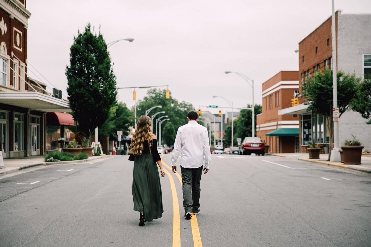 A couple walk down a city street in North Carolina.