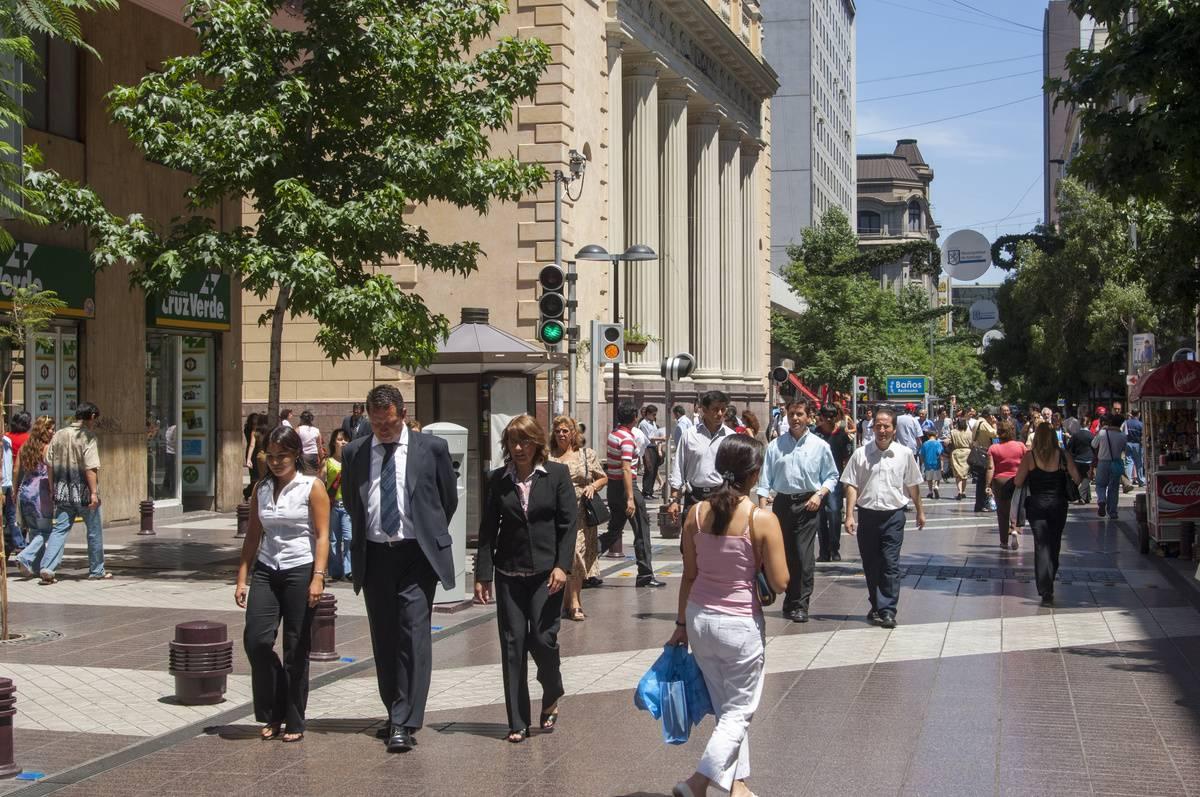People walk across a busy street in Santiago, Chile.