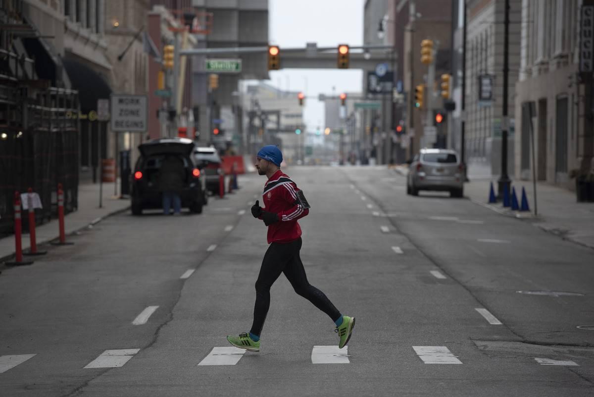 A man jogs across the street in Detroit, Michigan.