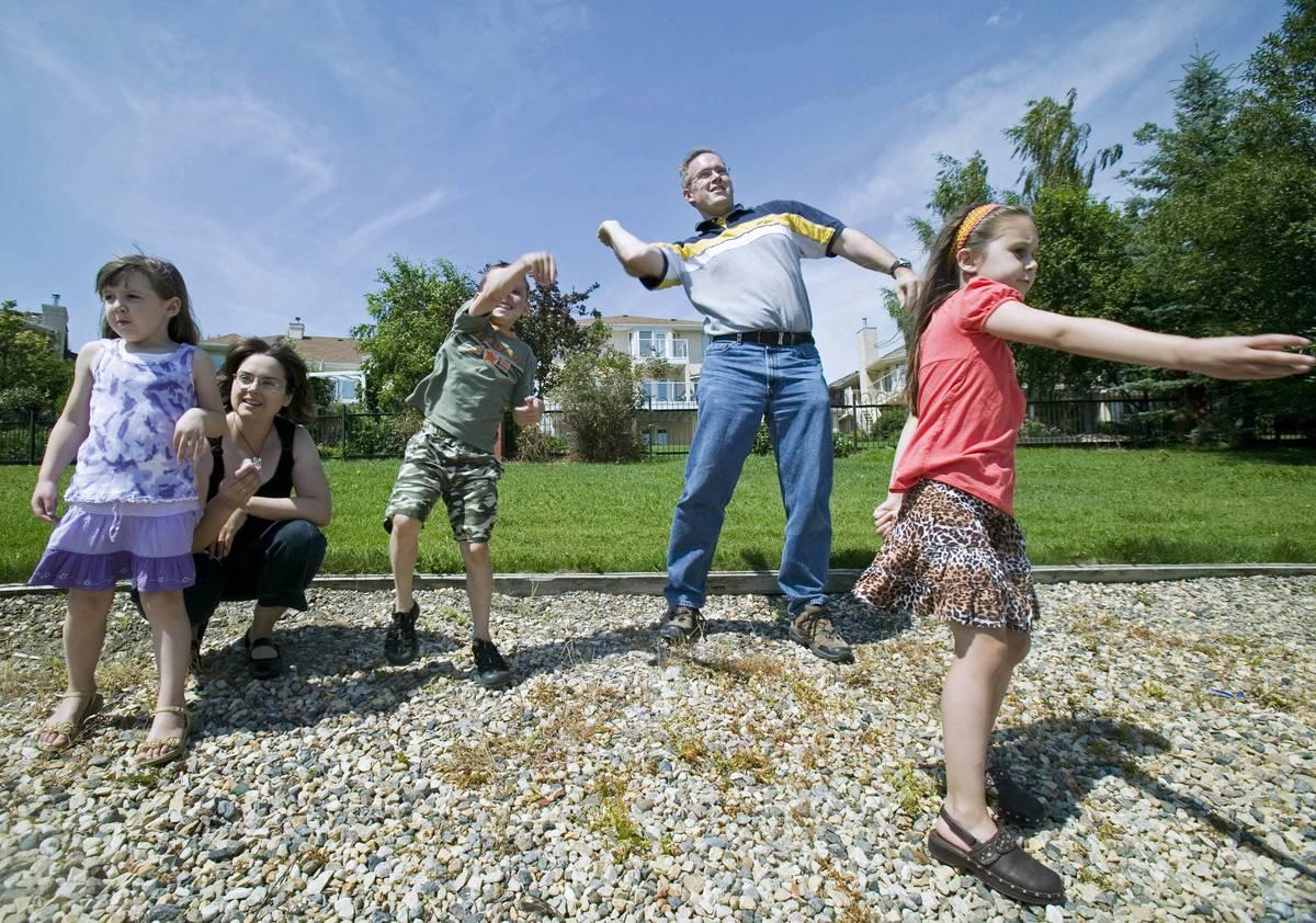 A family skips rocks across a lake together in Saskatchewan, Canada.