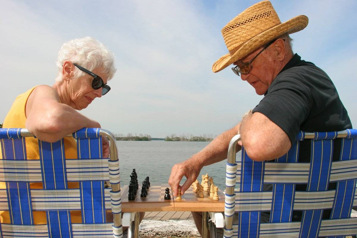 An elderly couple plays chess on the coast of Florida.