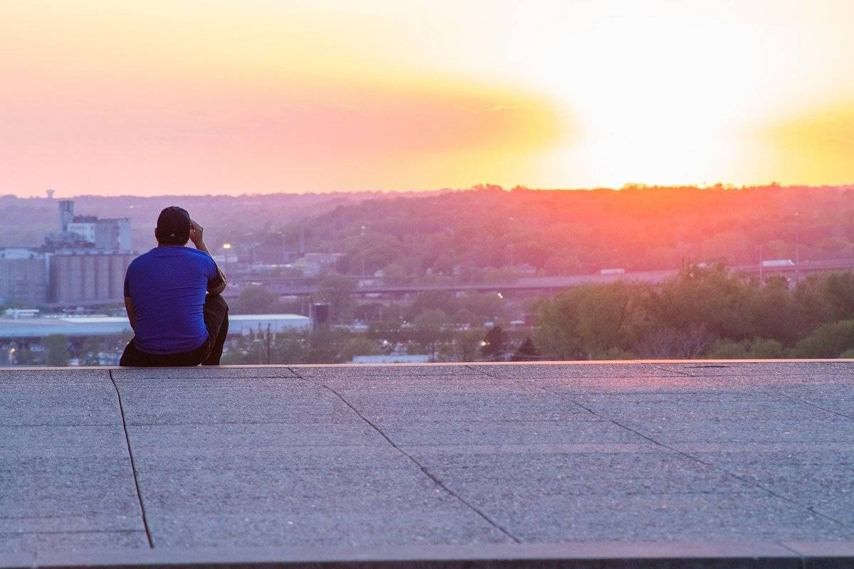 A man watches the sun set over Kansas City.
