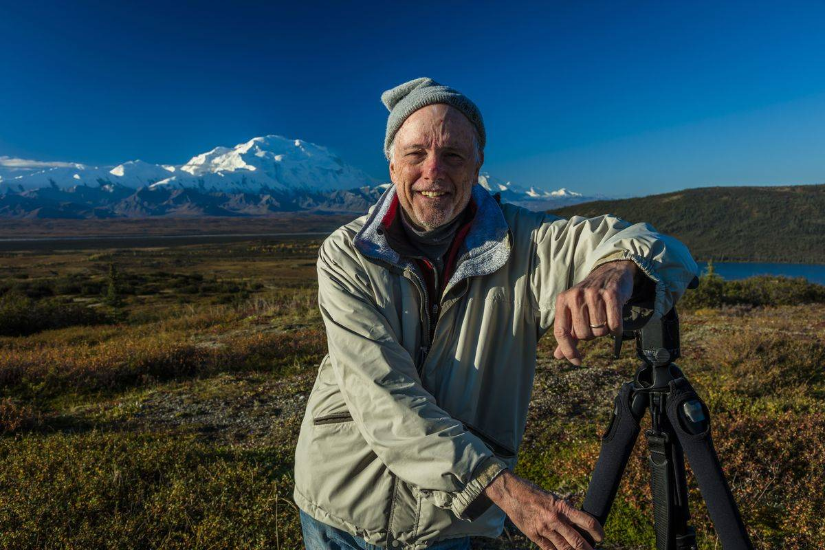 A photographer poses at famous Ansel Adams picture spot, in Wonder Lake, Alaska.