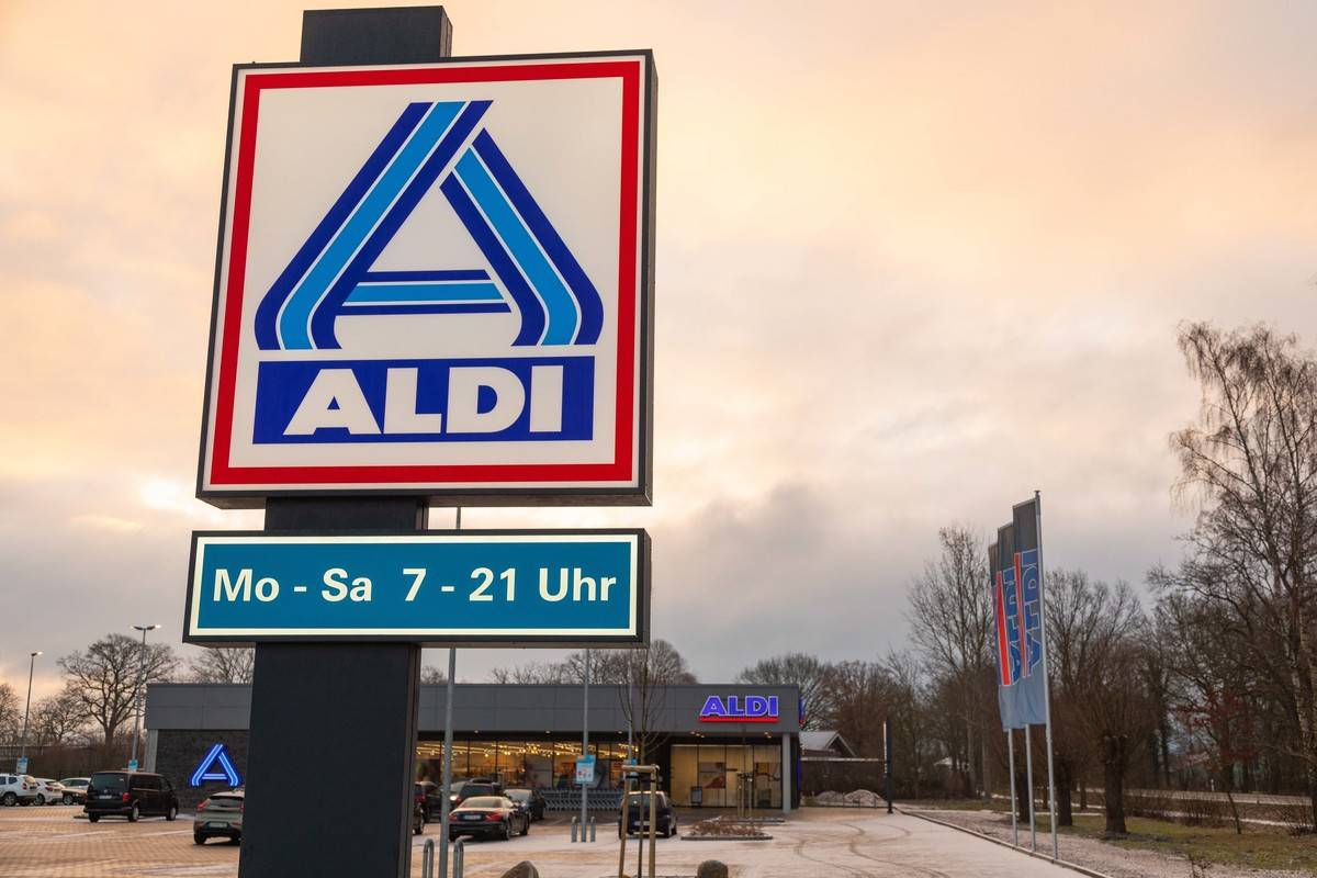 A sign is seen on the street corner of an Aldi store.