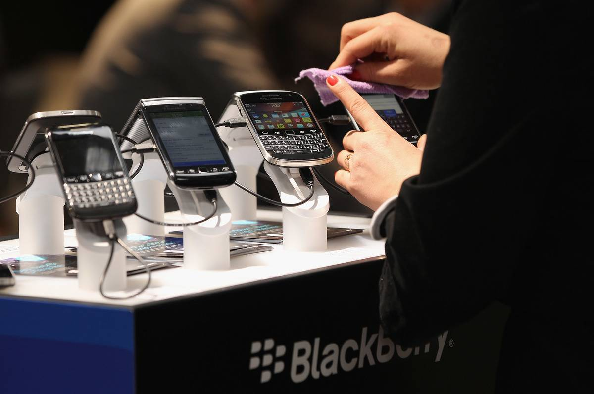 A woman checks out a Blackberry cell phone on display.