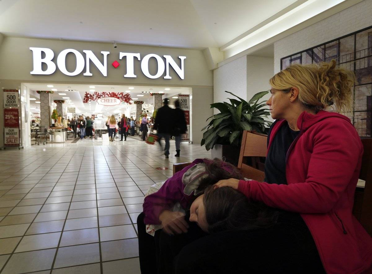 A mom and her daughter sit down to rest near a Bon-Ton store in a mall.