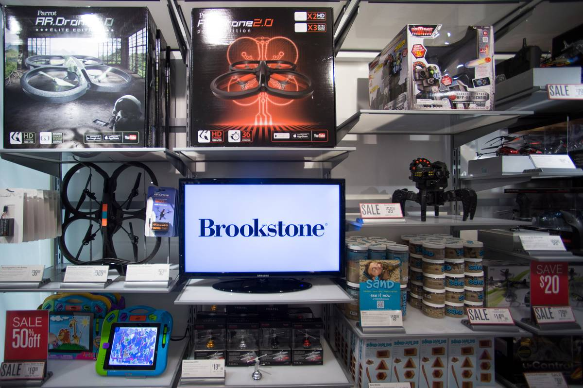 The shelves of a Brookstone store feature a monitor with the store logo.