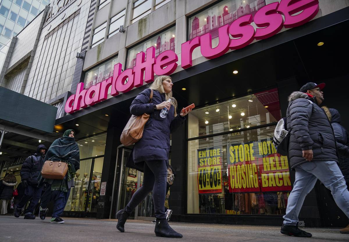 People walk by a Charlotte Russe store that is hosting a closing sale.
