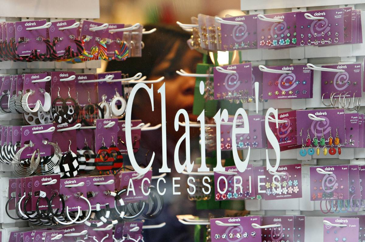 The Claire's logo is printed on a storefront window in front of displayed earrings.