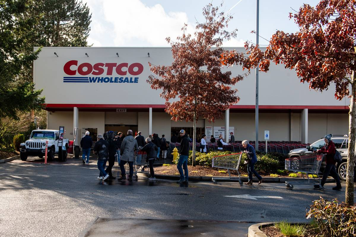 Shoppers wait in line for a Costco Wholesale to open.