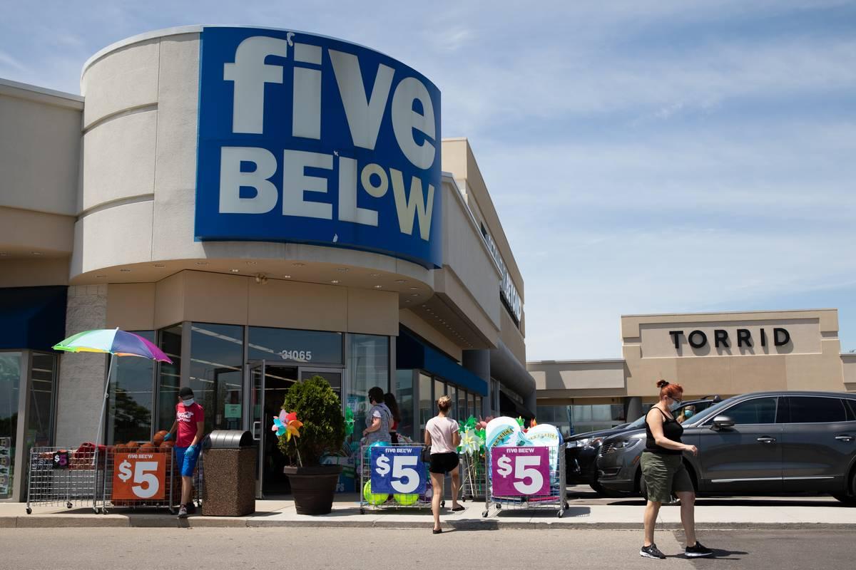 Customers walk outside of a Five Below store.