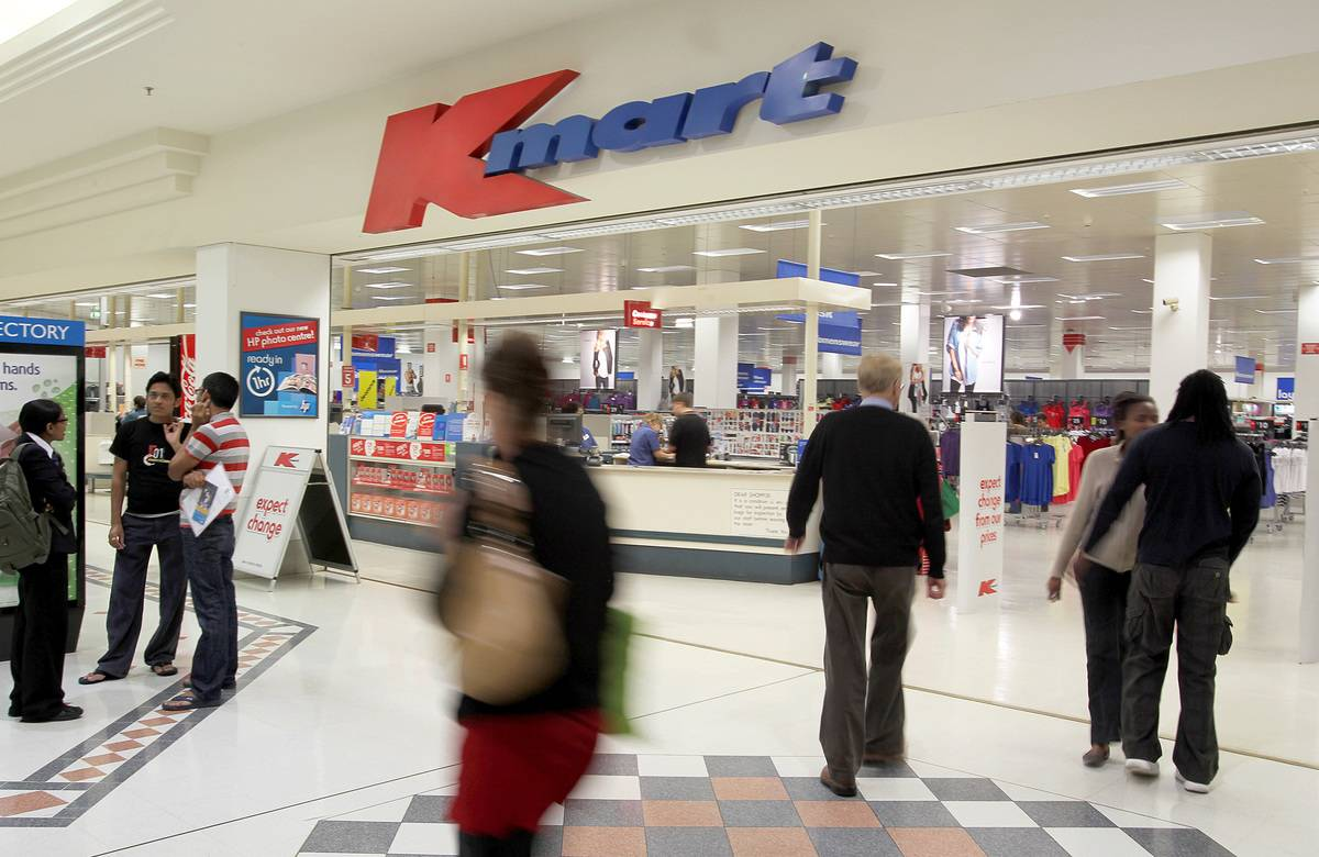 Shoppers walk past a Kmart in a mall.