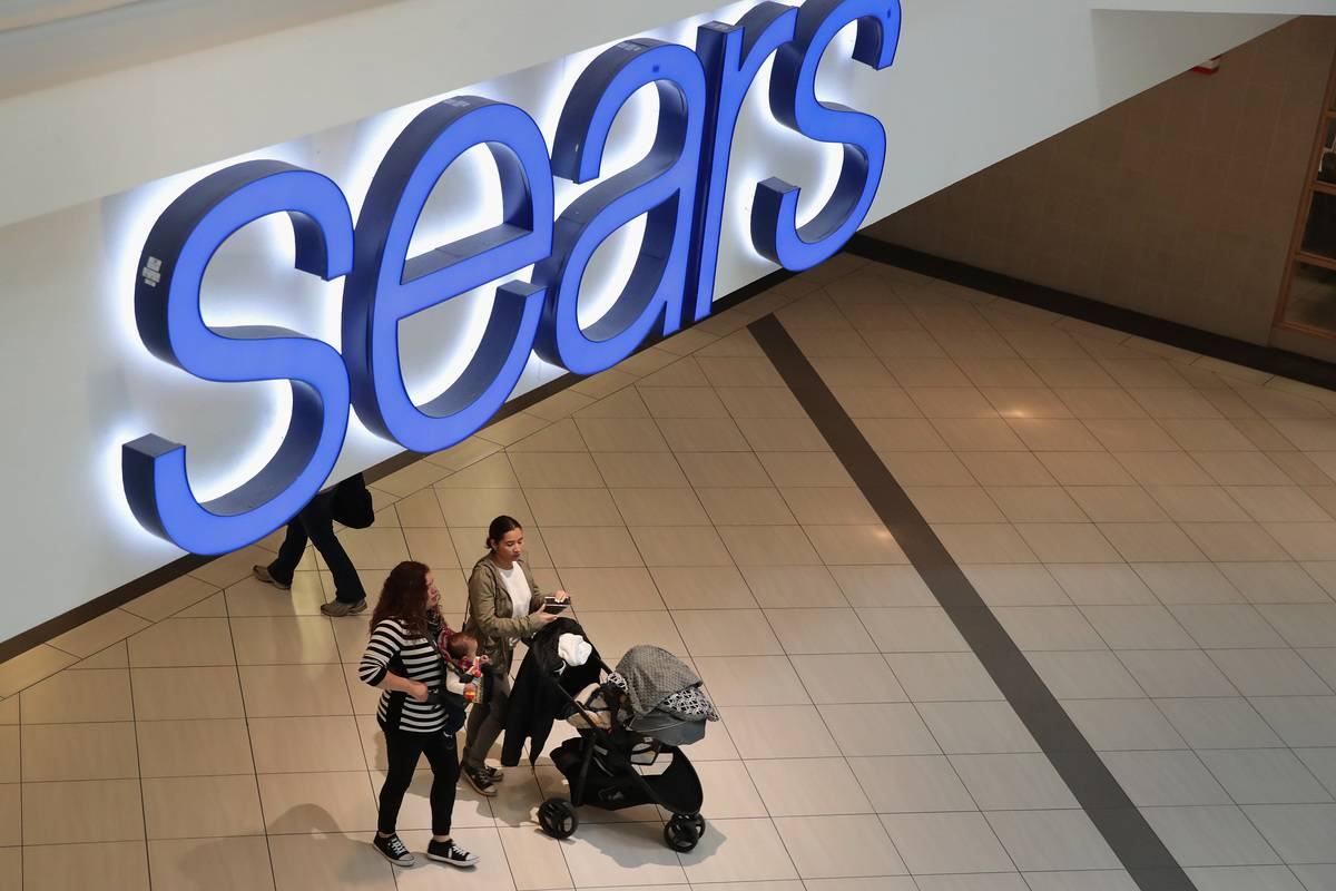 People exist a Sears store in a mall.