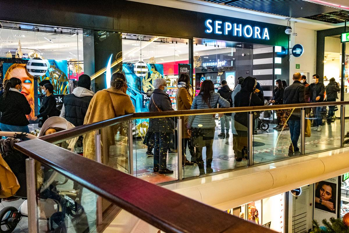 A line forms outside of a Sephora store in a mall.