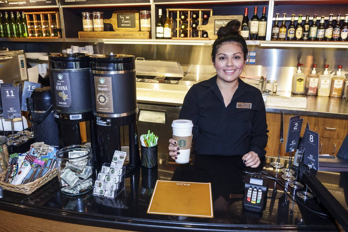 A Starbucks Coffee barista serving a cup of coffee.
