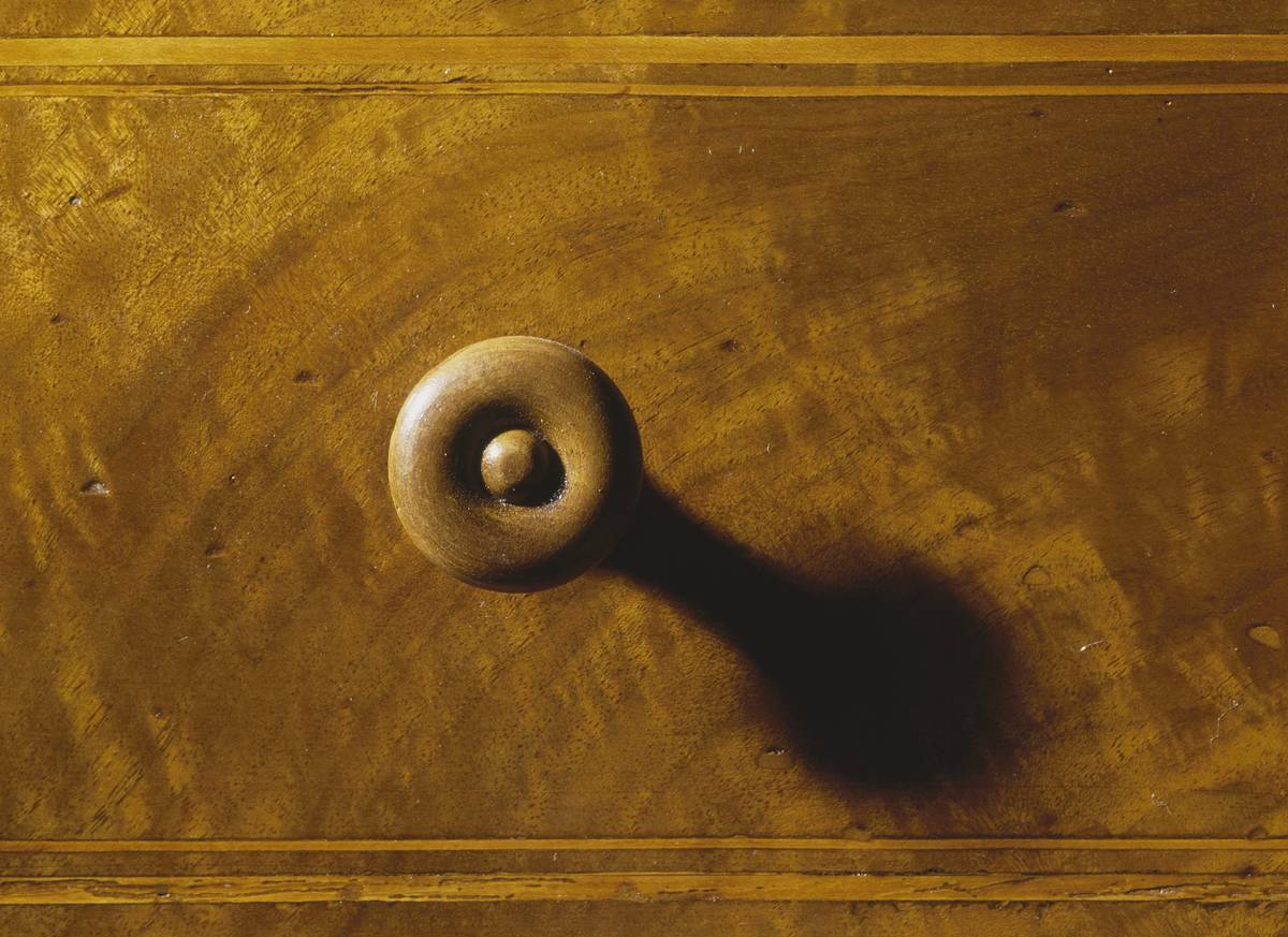 A wooden knob is on the chest of an 1840 dresser.