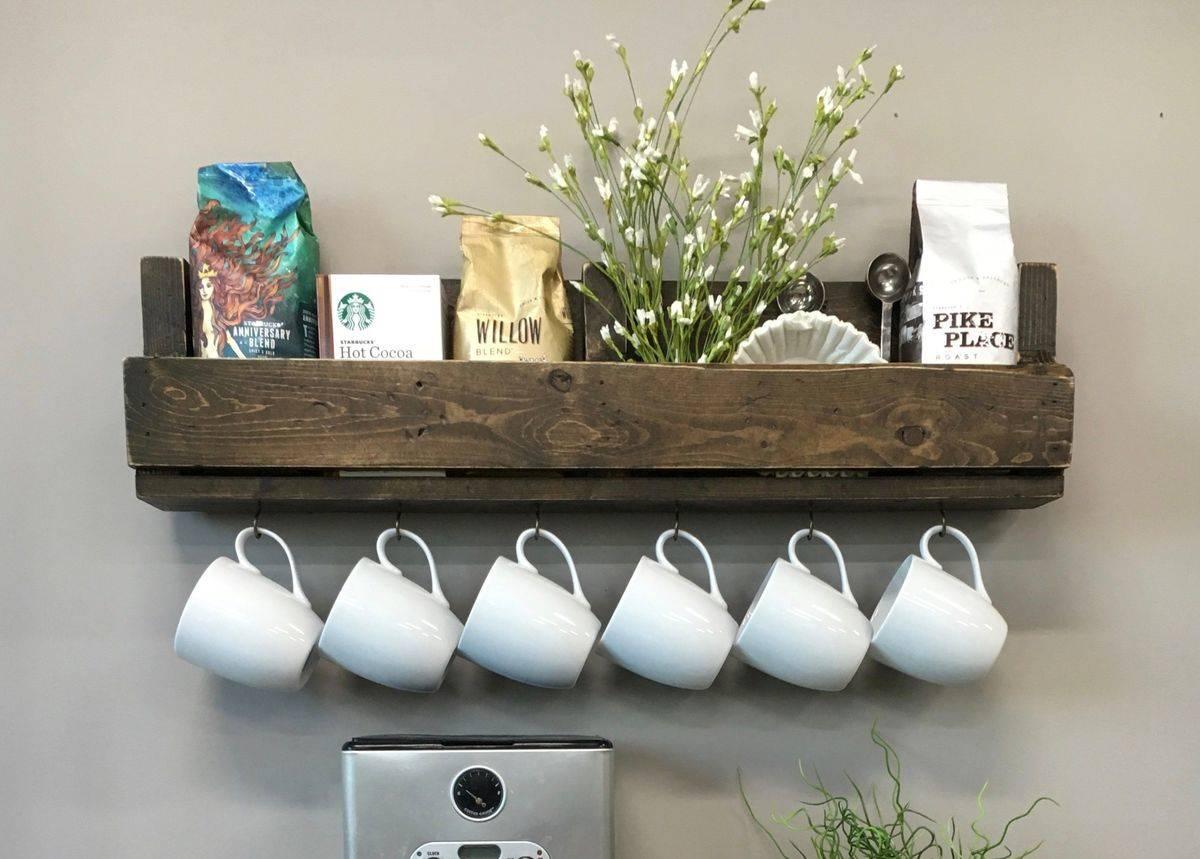White mugs hang from hooks underneath a wall shelf.