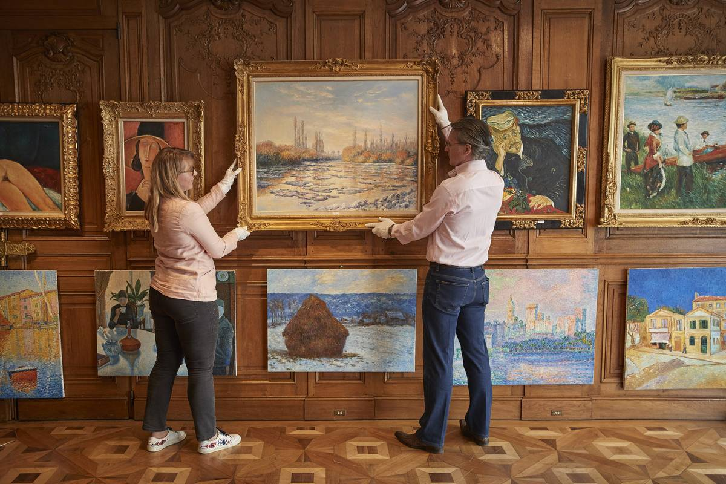 Two people hang art onto a wall.