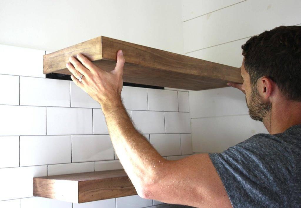 A man installs floating wall shelves.
