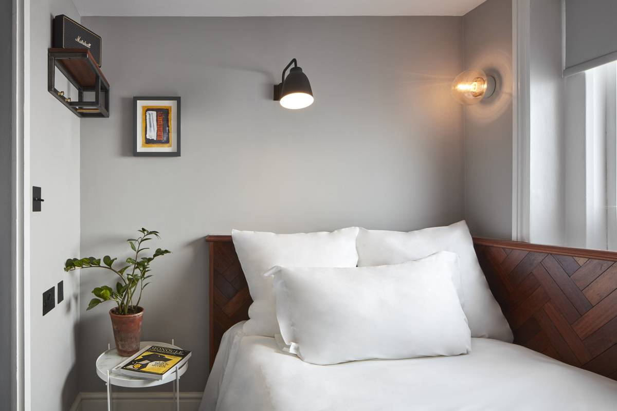 A small bedroom is decorated with a small painting, hanging light, and small shelf.