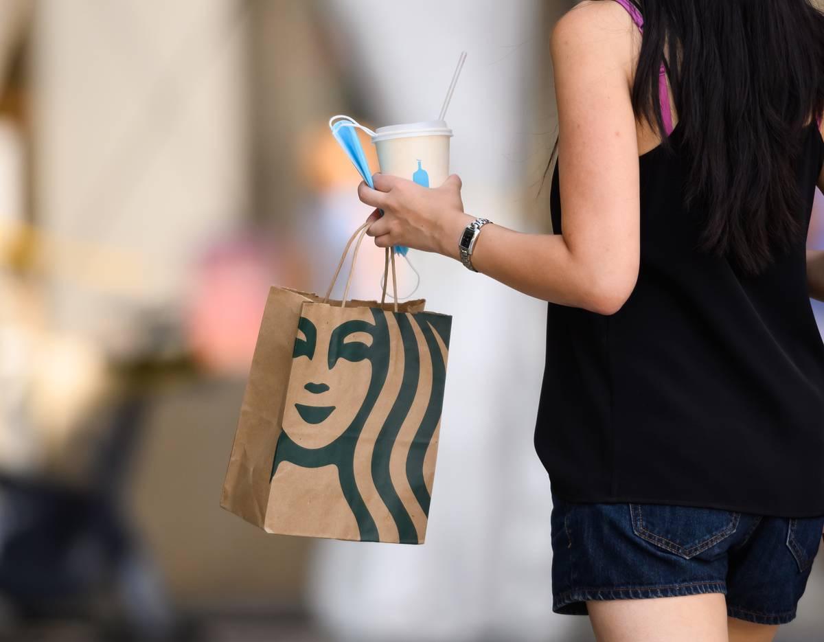 A woman carries around a Starbucks bag.