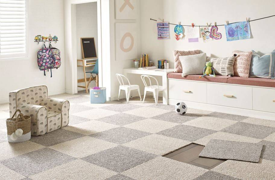 Temporary carpet squares are laid out in a child's playroom.