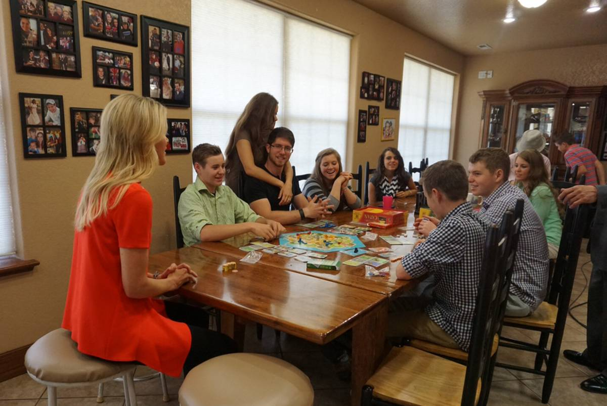 Members of the Duggar family sit at the table to play games with a reporter.