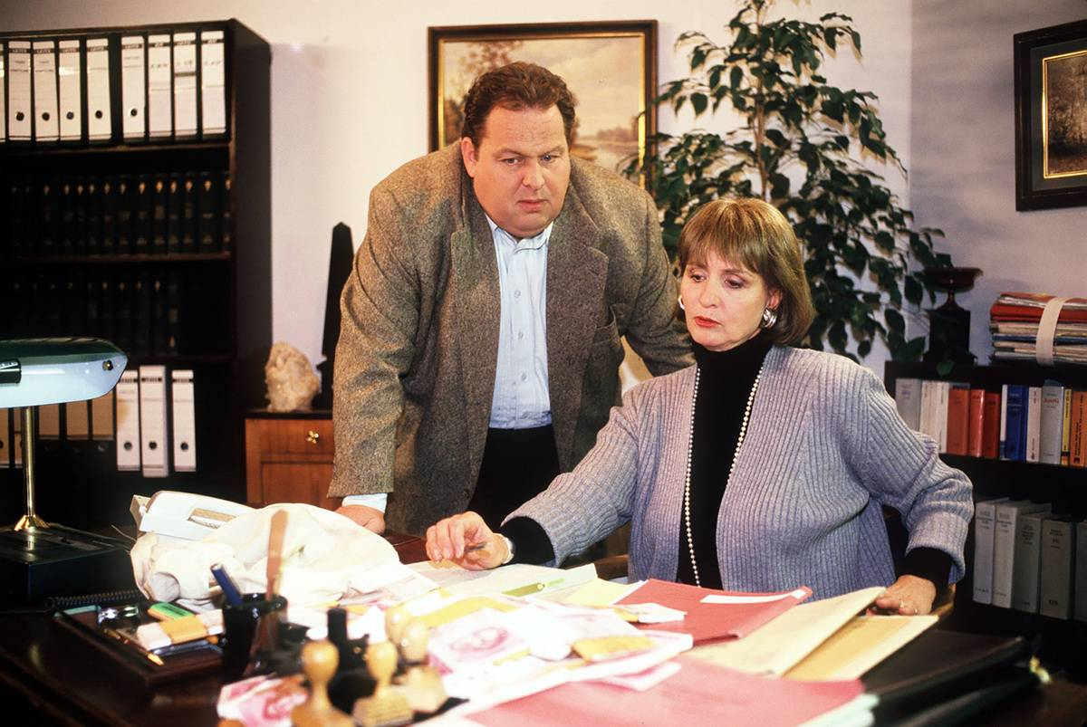 A financial advisor works with a woman on her budget.