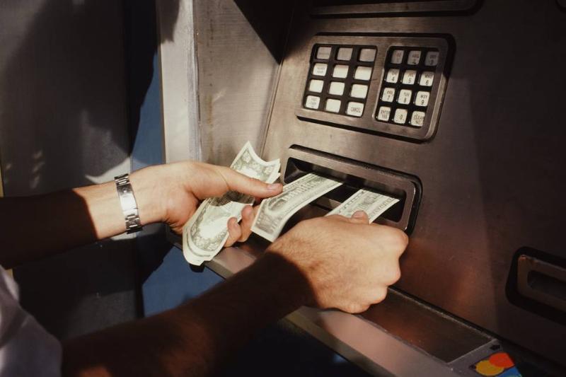 A man receives cash from an atm.