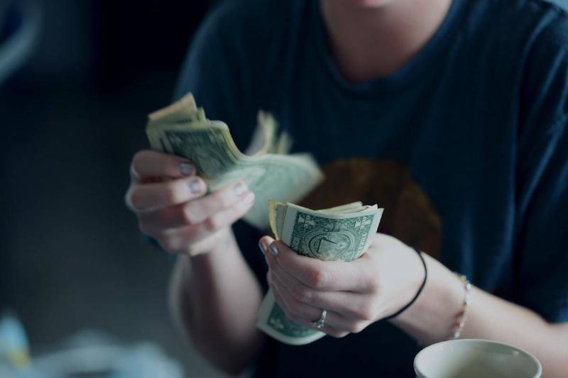 A man counts dollar bills.