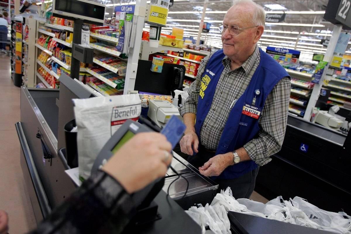 An elderly man checks out a customer at Walmart.