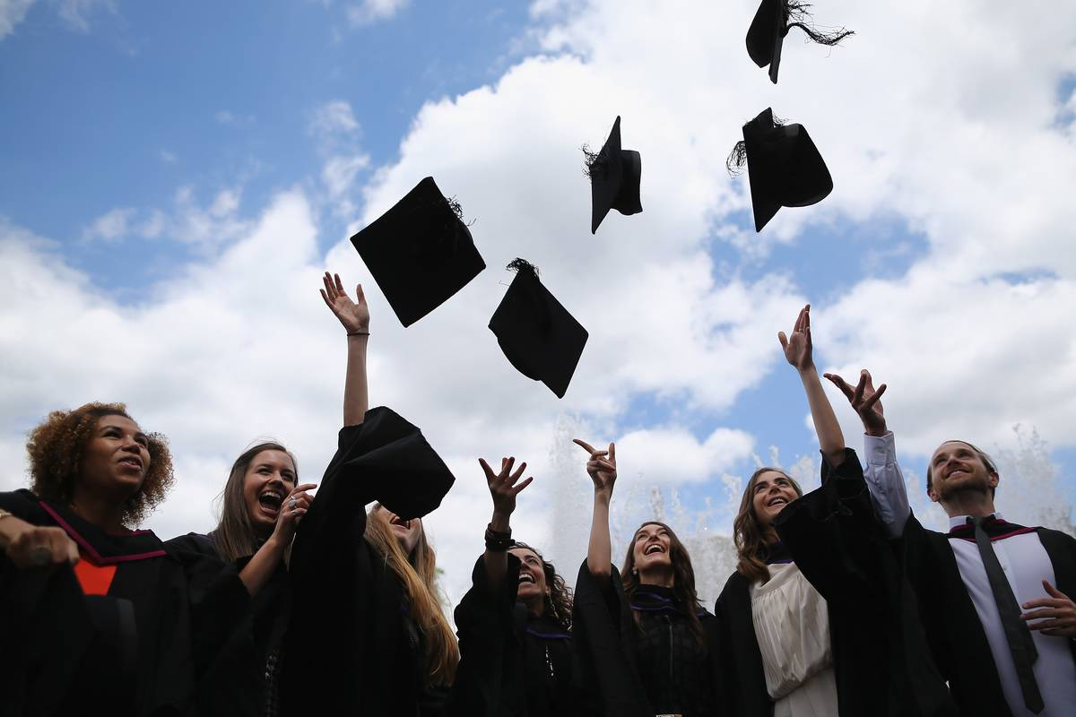 University graduates throw their caps in the air in celebration.