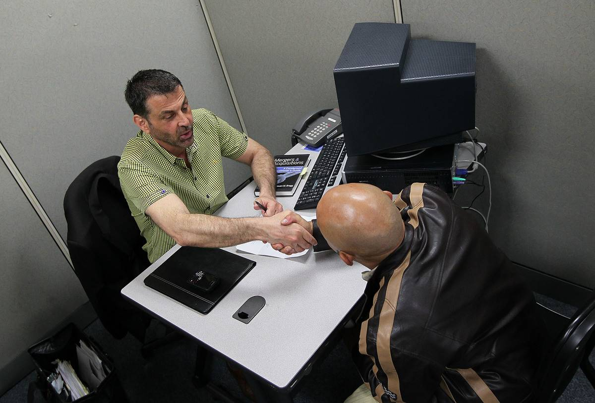 An employer shakes an applicant's hand during a job interview.
