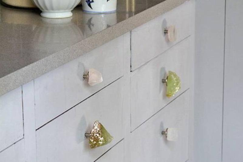 A variety of crystal knobs are on kitchen drawers.