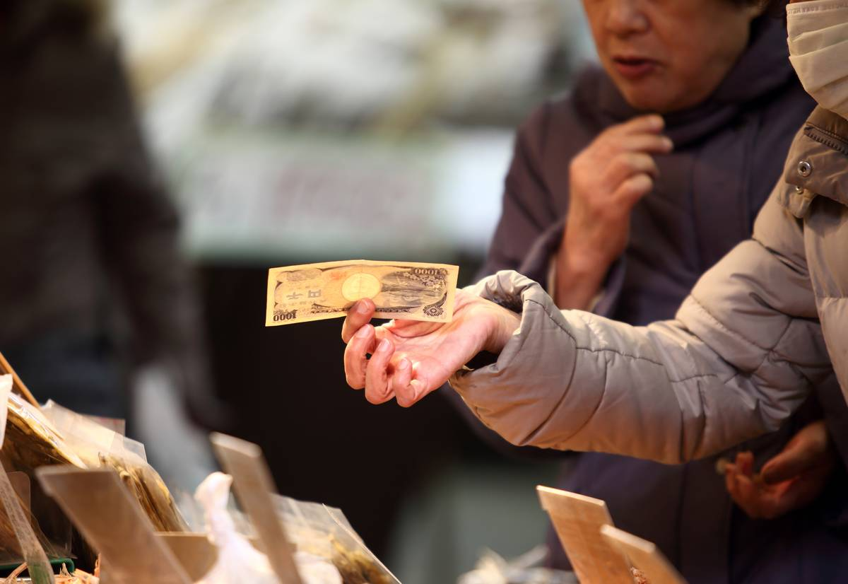 A retired woman hands out money to pay for something in Japan.