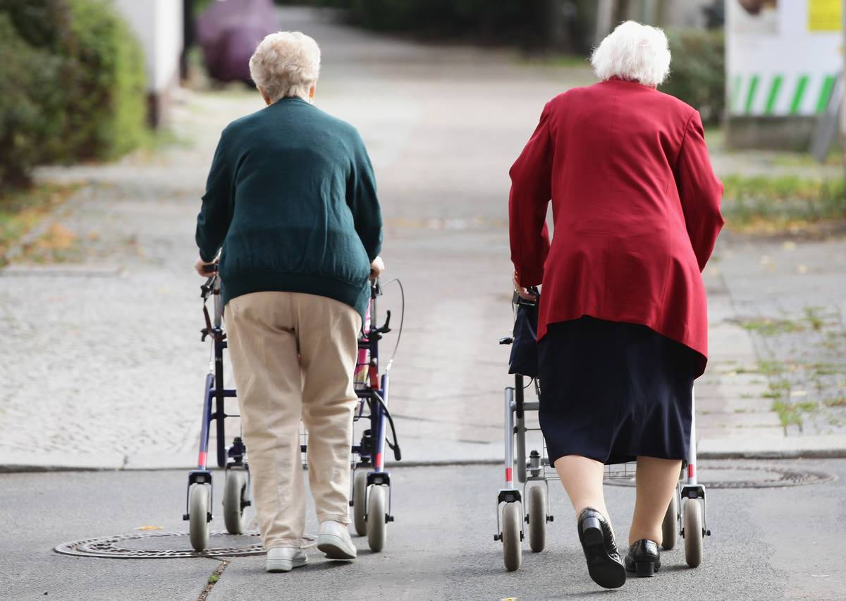 Retired women walk together with shopping carts.