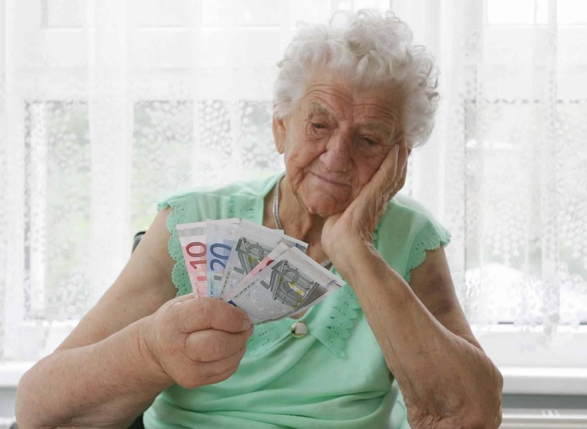 An elderly women stars that the Euros she holds.