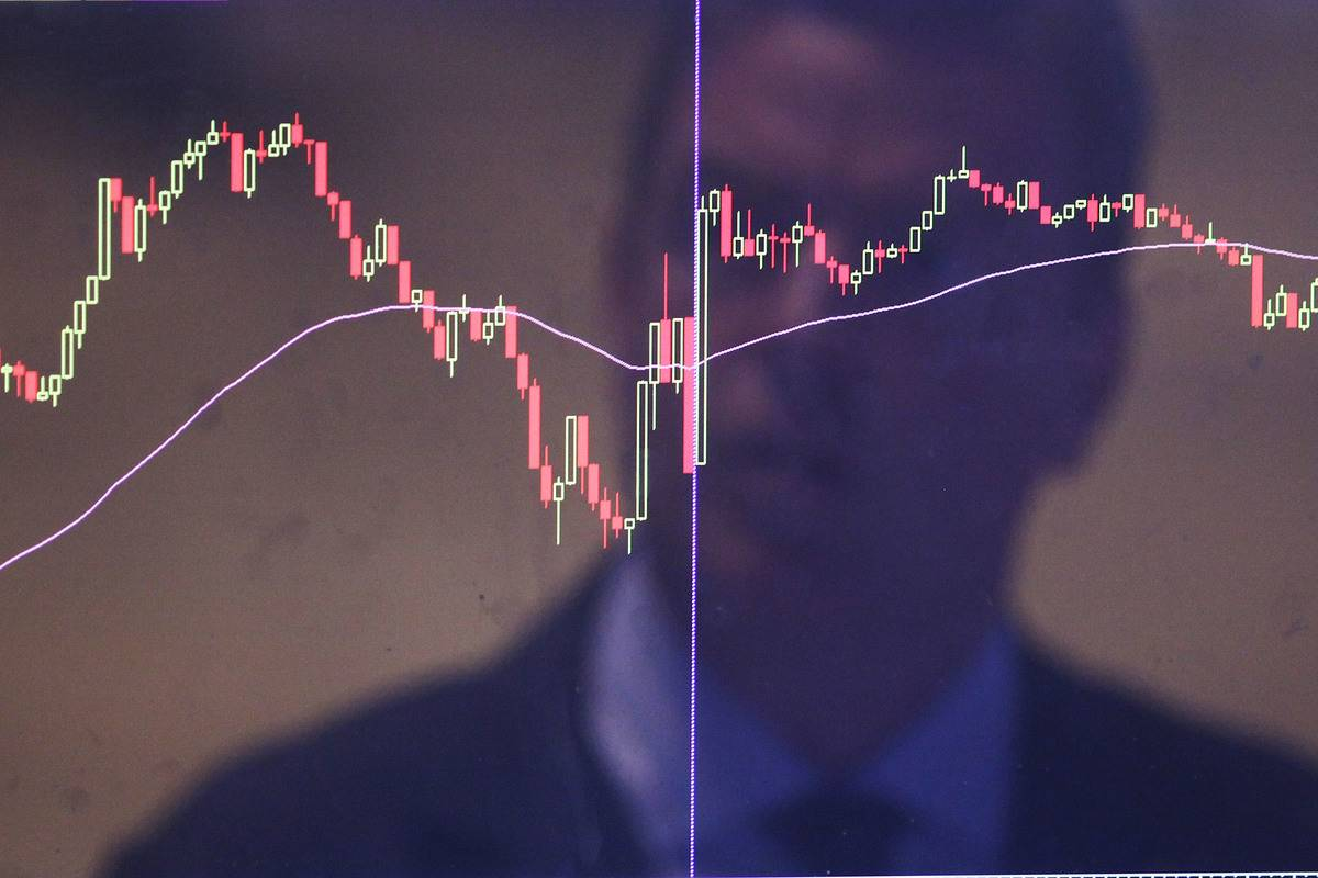 A man watches the stocks plummet and rise on a graph.